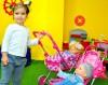 Девочка играет с куклой в коляске